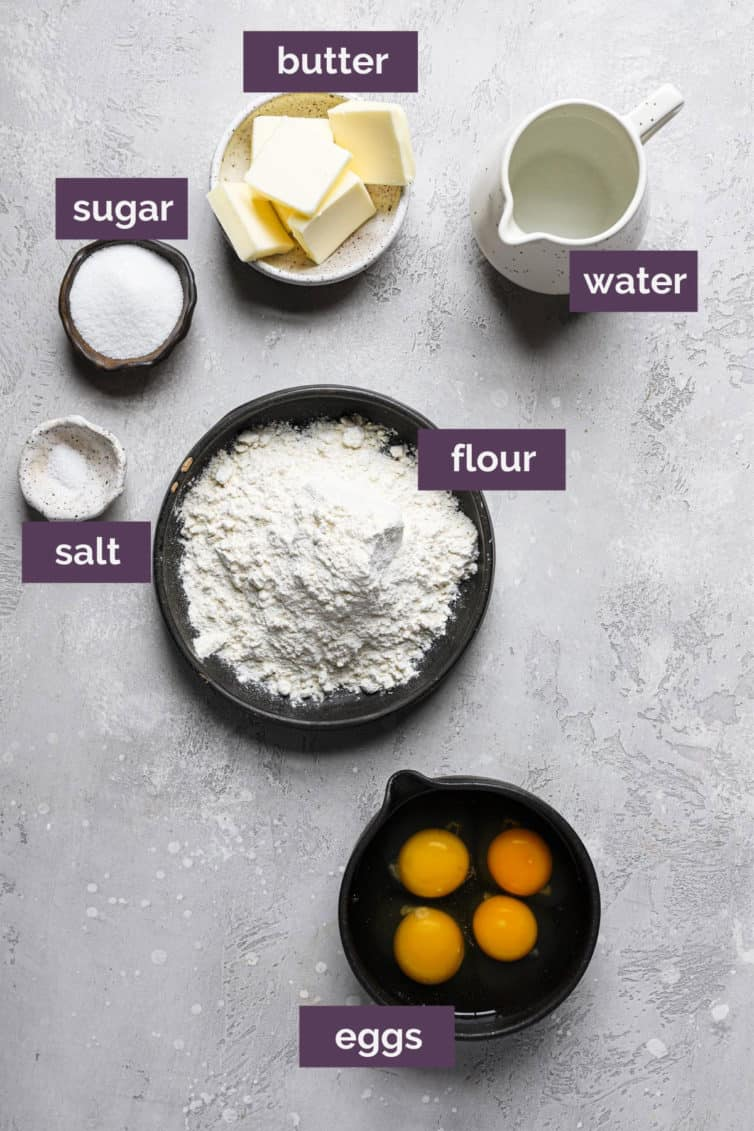 Ingredients for profiteroles on a white grey counter labeled with purple rectangles.