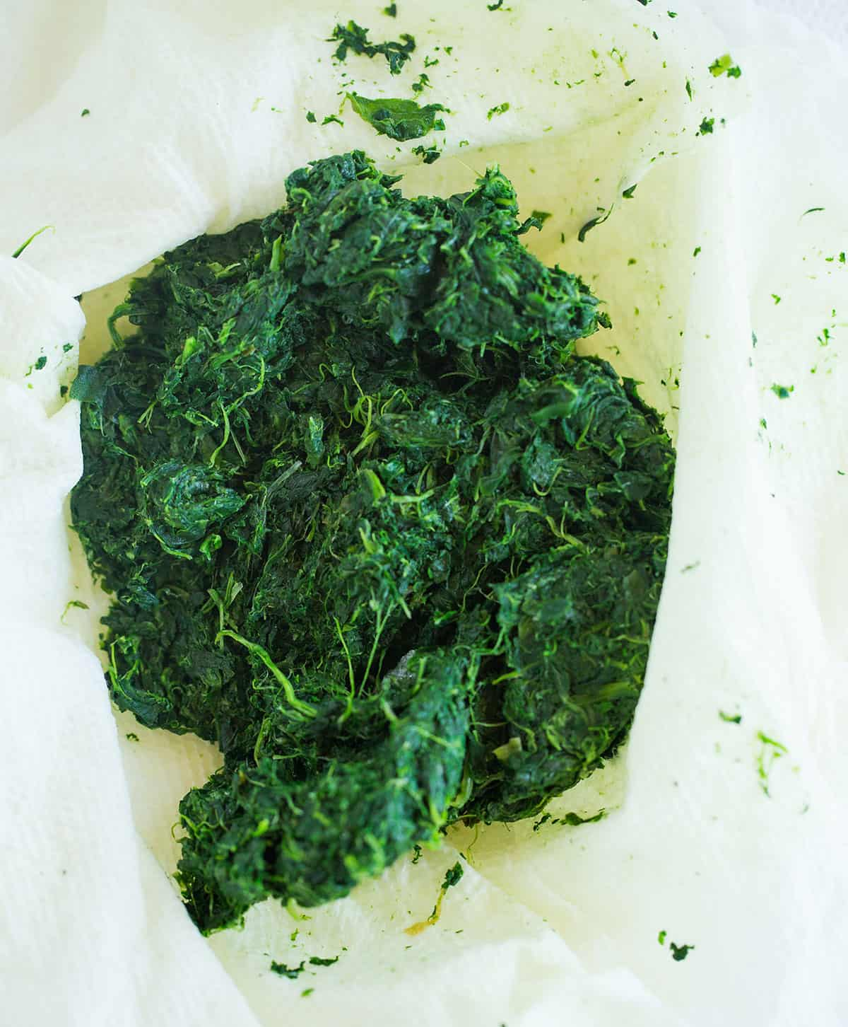 A dish towel with spinach after draining the moisture in a towel.