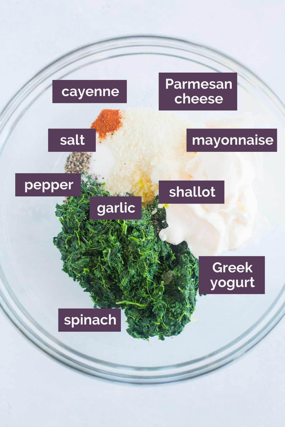 Ingredients for spinach dip in a glass bowl with purple labels naming the ingredeints.