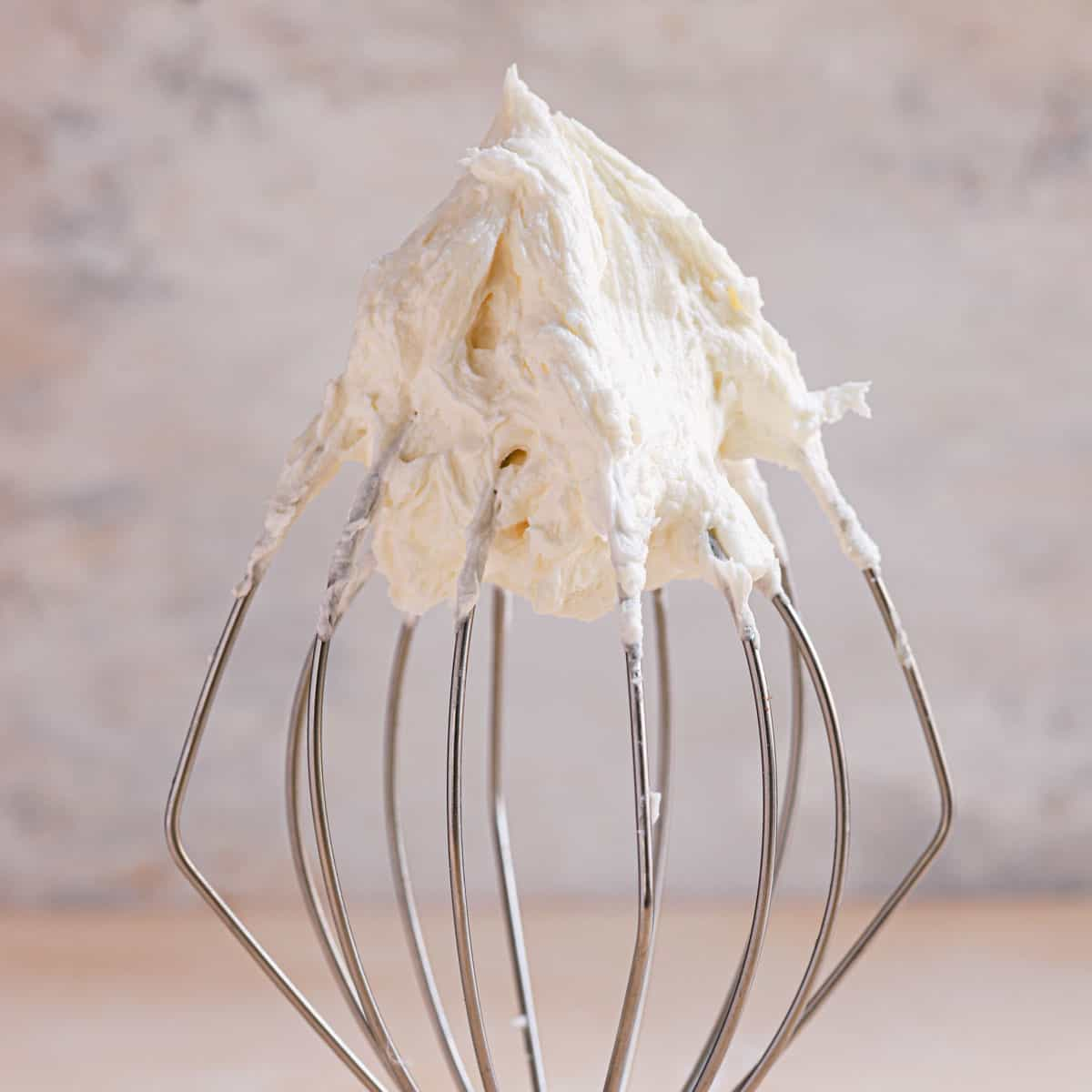 A square photo of vanilla buttercream frosting on a wire whisk.