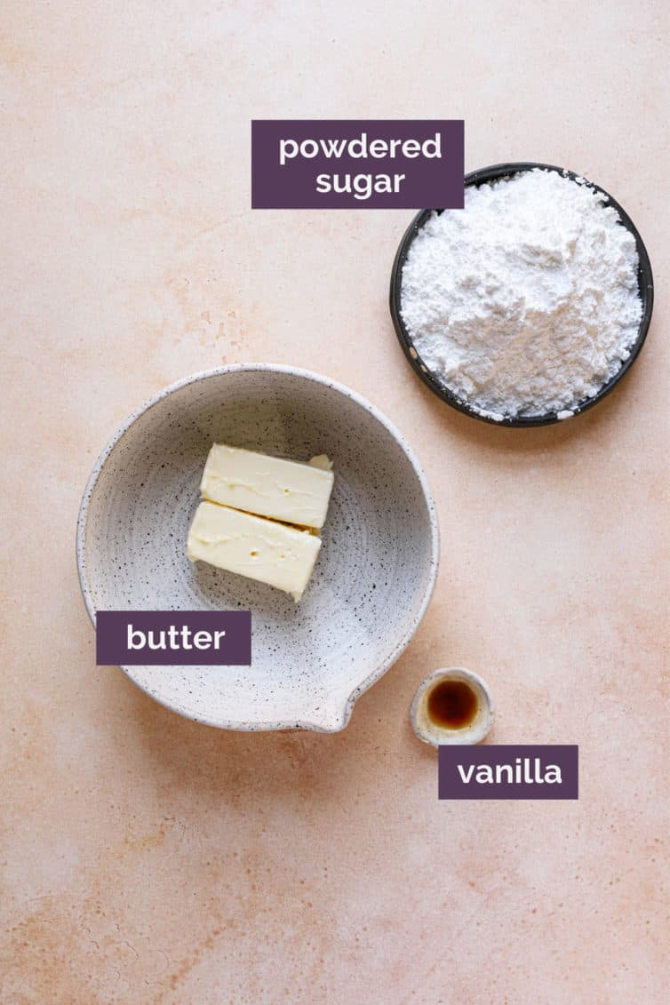 Ingredients for vanilla buttercream frosting in bowls with purple labels.
