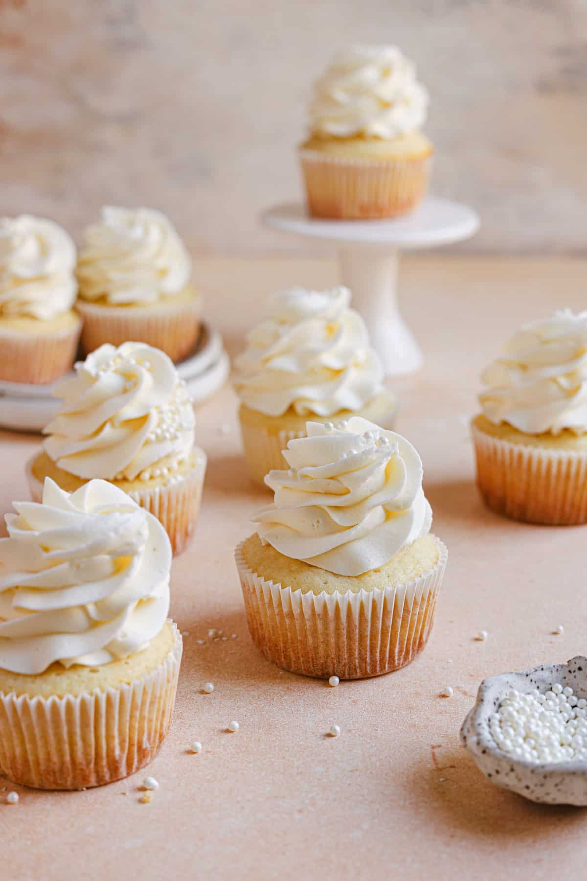Moist vanilla cupcakes on a counter with a cupcake on a cake stand in the back.