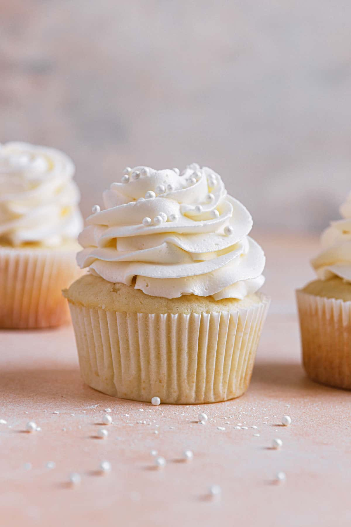 A vanilla cupcake with vanilla frosting and sprinkles in the middle another to the right and one in the back left.