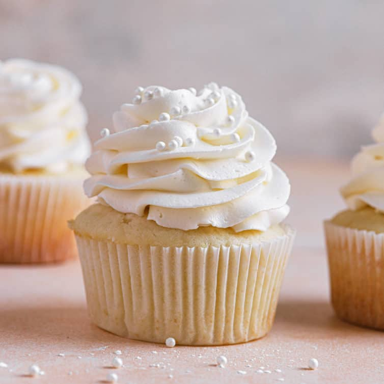 A square image of a vanilla cupcake with vanilla frosting with another in the back left and one to the right.