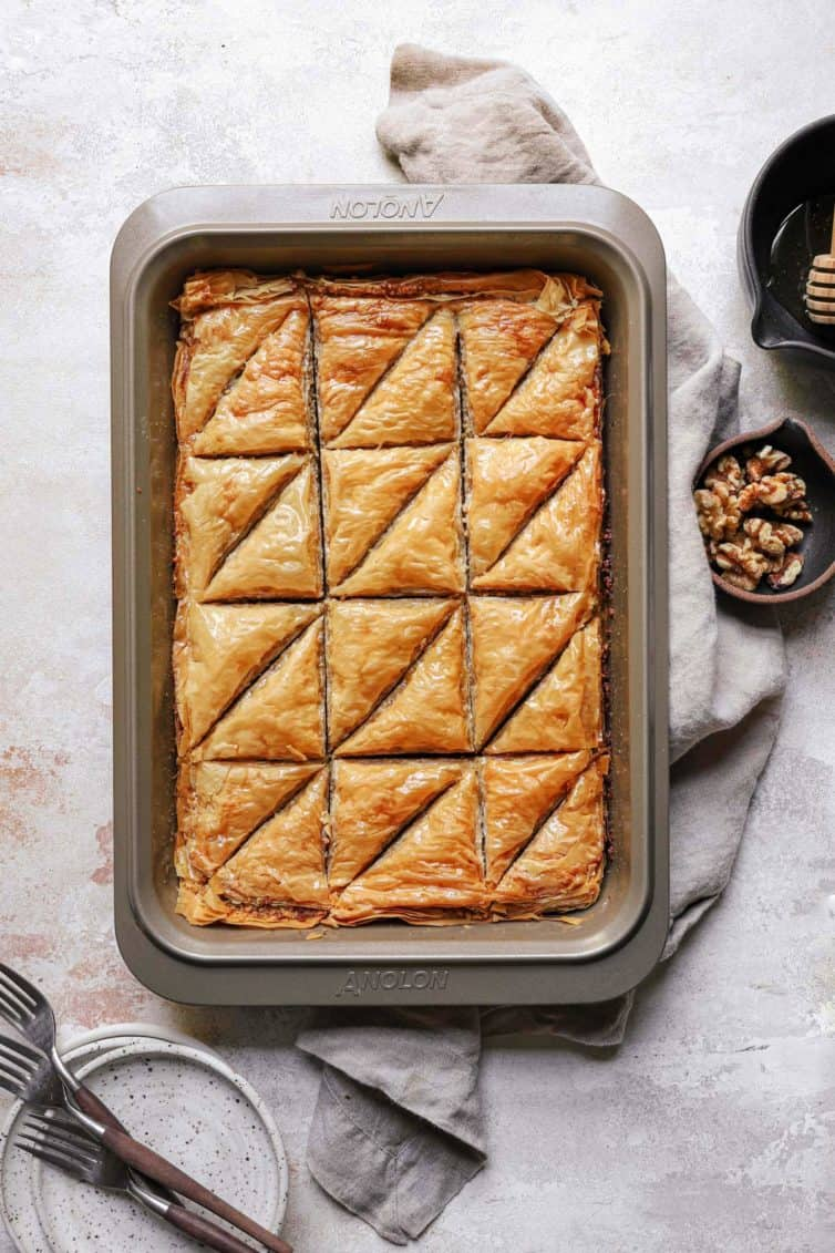 A top down photo of baklava on a counter with a dish towel and a small bowl of walnuts to the right.