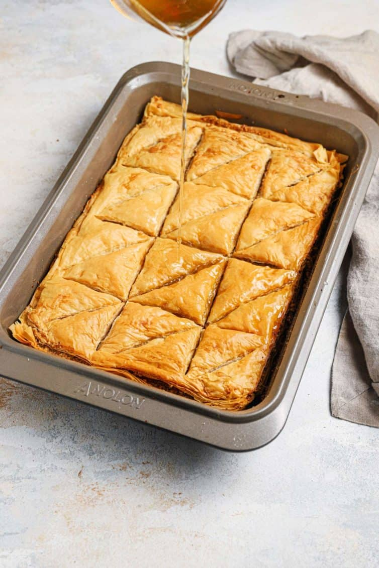 Syrup being poured over a baking pan of baklava with a towel in the back right.