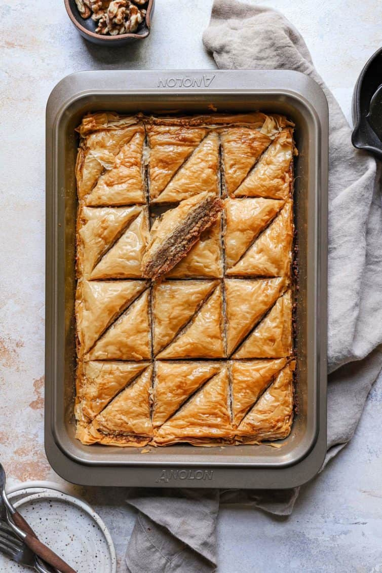 Baklava in a baking dray cut into rectangles with a towel under the baking tray.