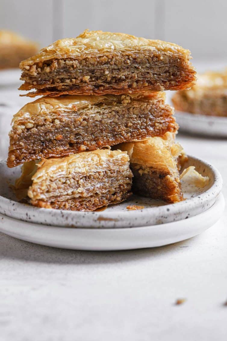 A stack of baklava triangles on white plates.