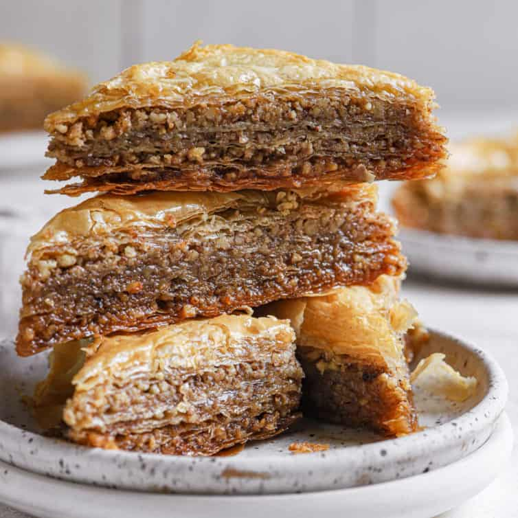 A stack of 3 slices of baklava on a white plate.