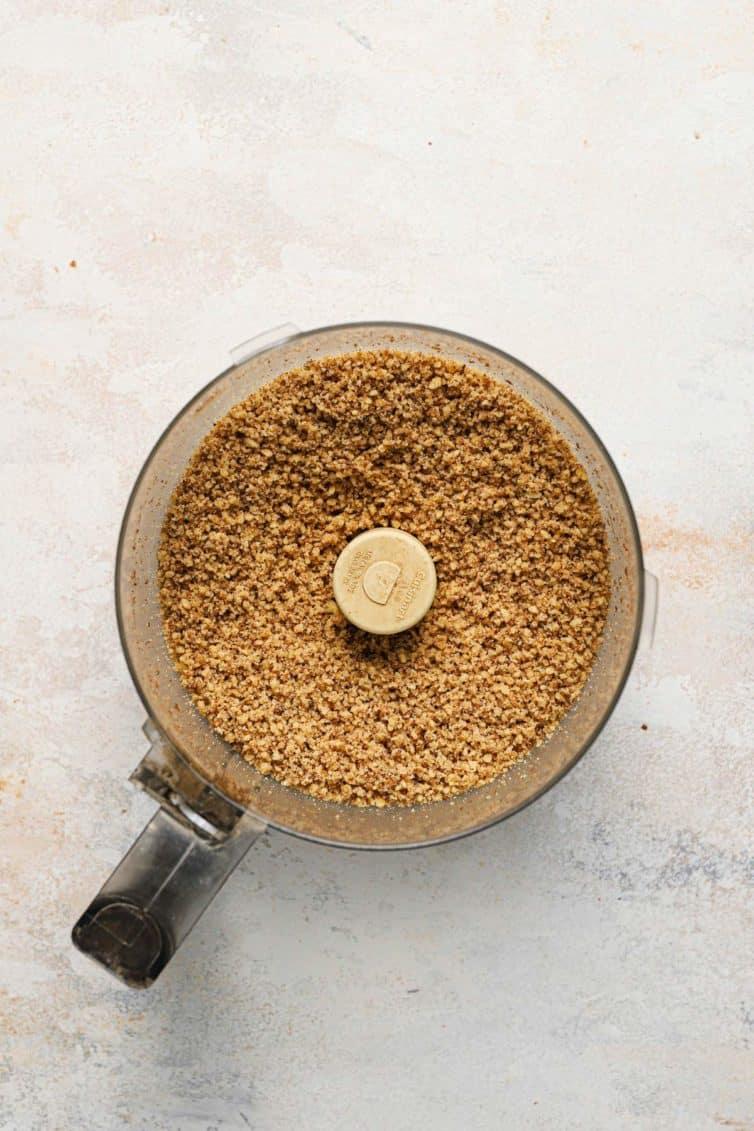 A food processor with bits of walnut filling.
