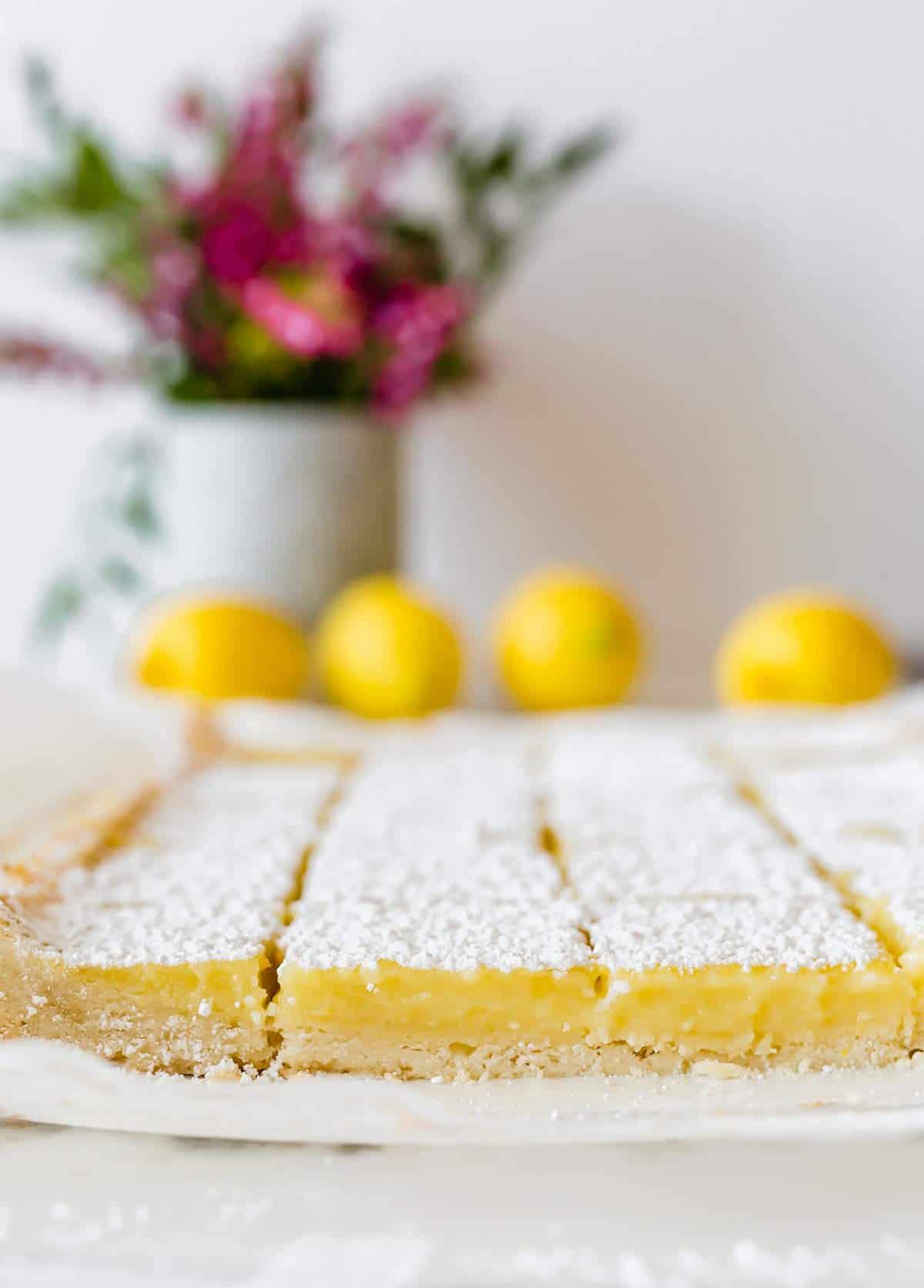 Lemon bars sliced into squares on a piece of parchment paper.