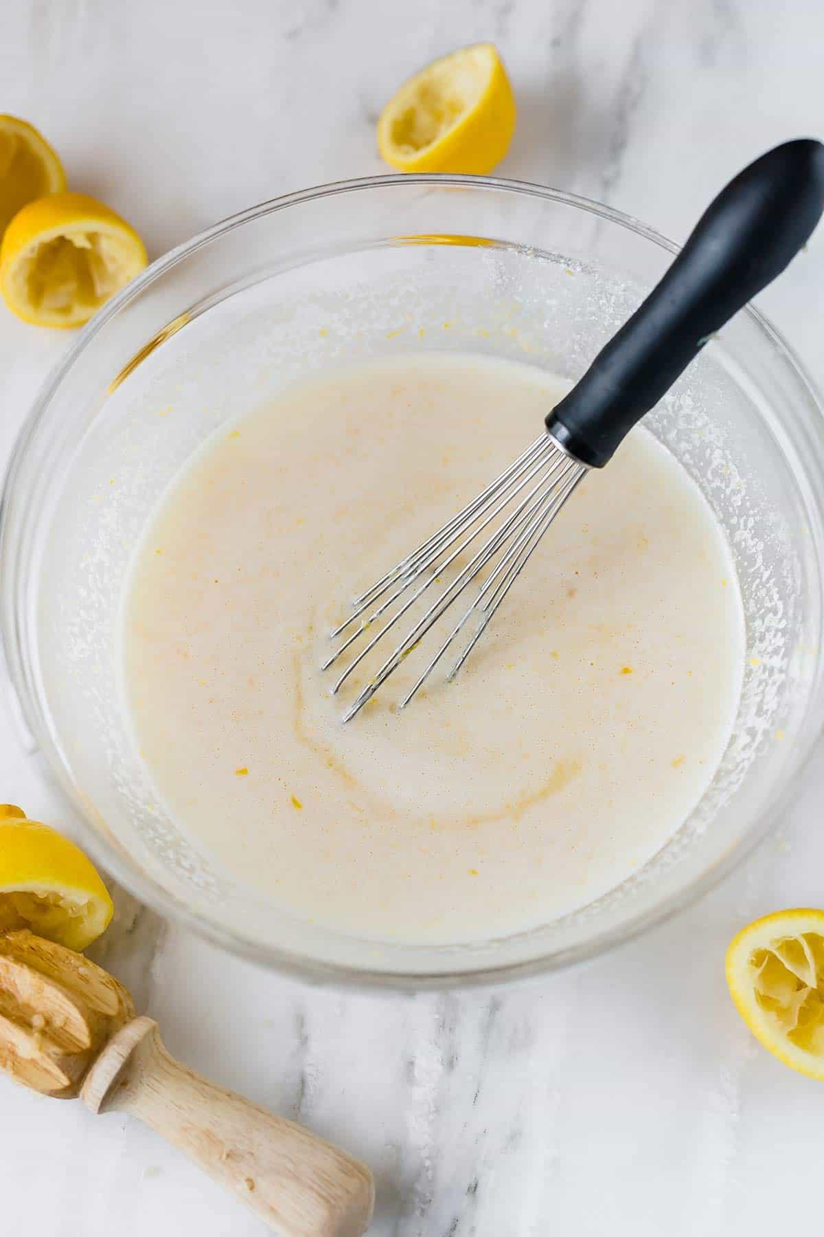 Filling for lemon bars whisked together in a bowl.