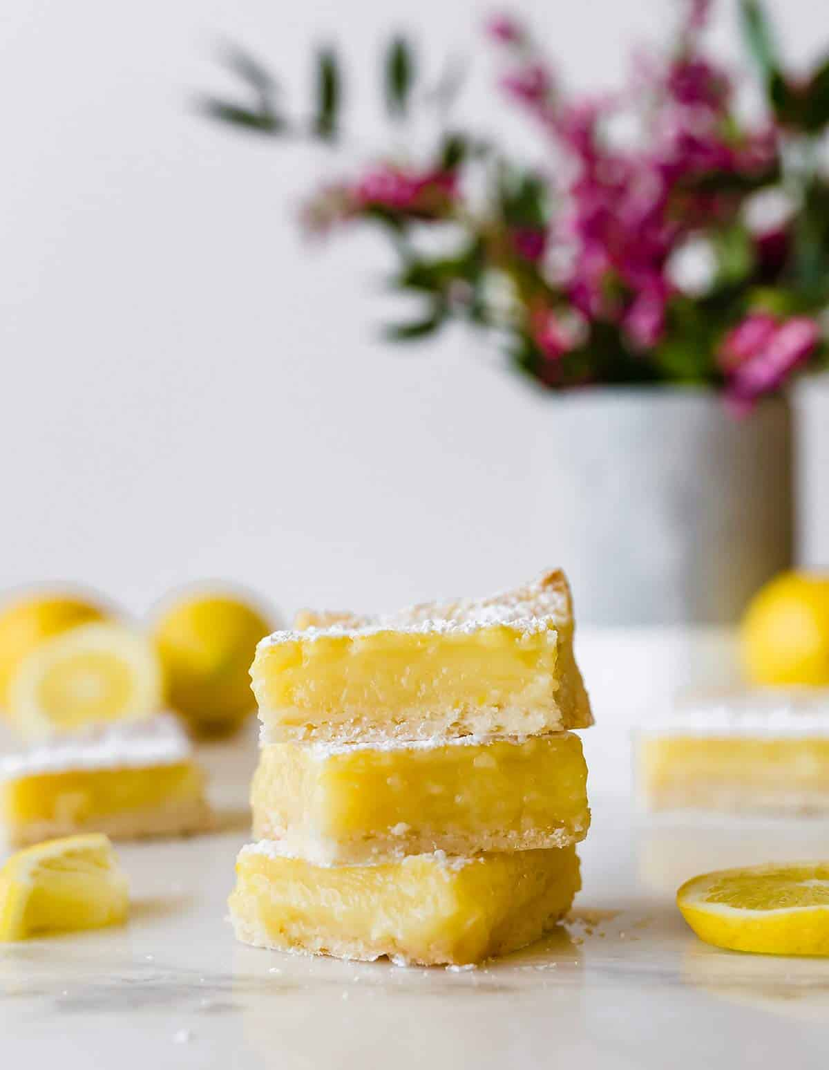 A stack of three lemon bars with cut lemons and a vase of flowers in the background.