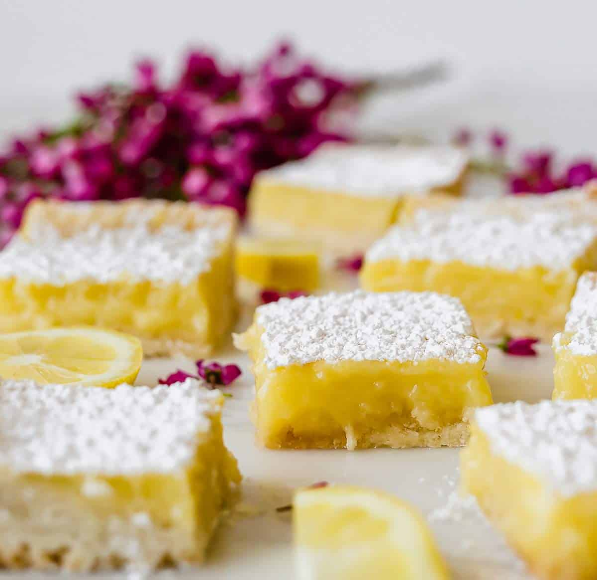 Lemon bars sitting on a piece of marble.
