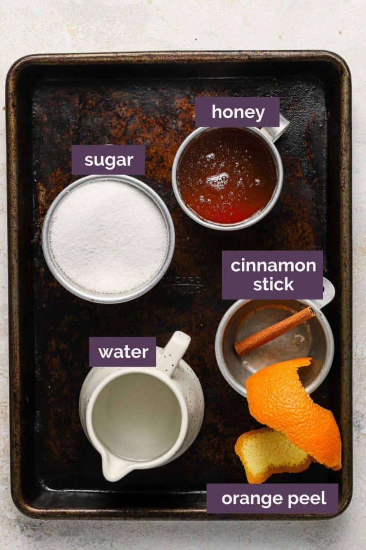 Ingredients for honey syrup on a baking sheet with purple labels telling what each ingredient is.