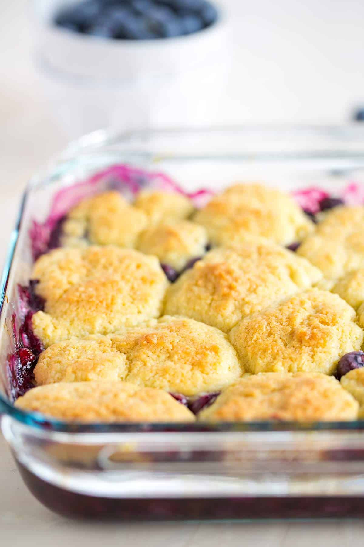 Blueberry cobbler in a glass pan just out of the oven.