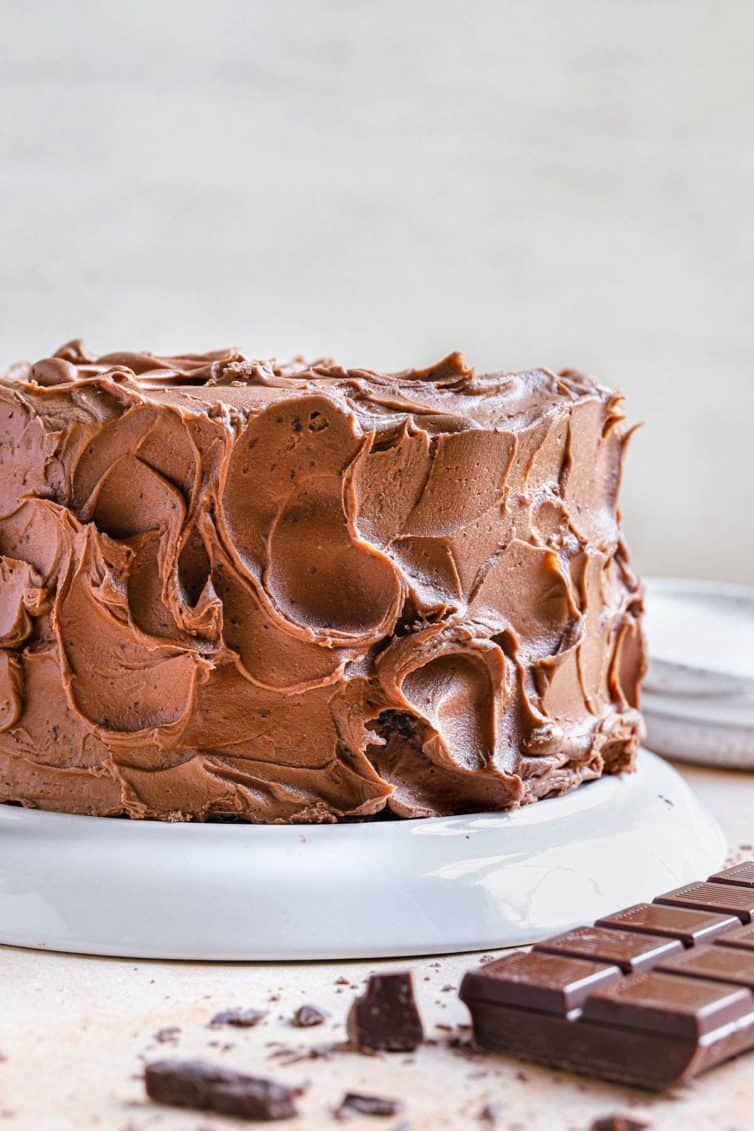 A full chocolate cake coated in chocolate frosting with a chocolate bar to the bottom right.