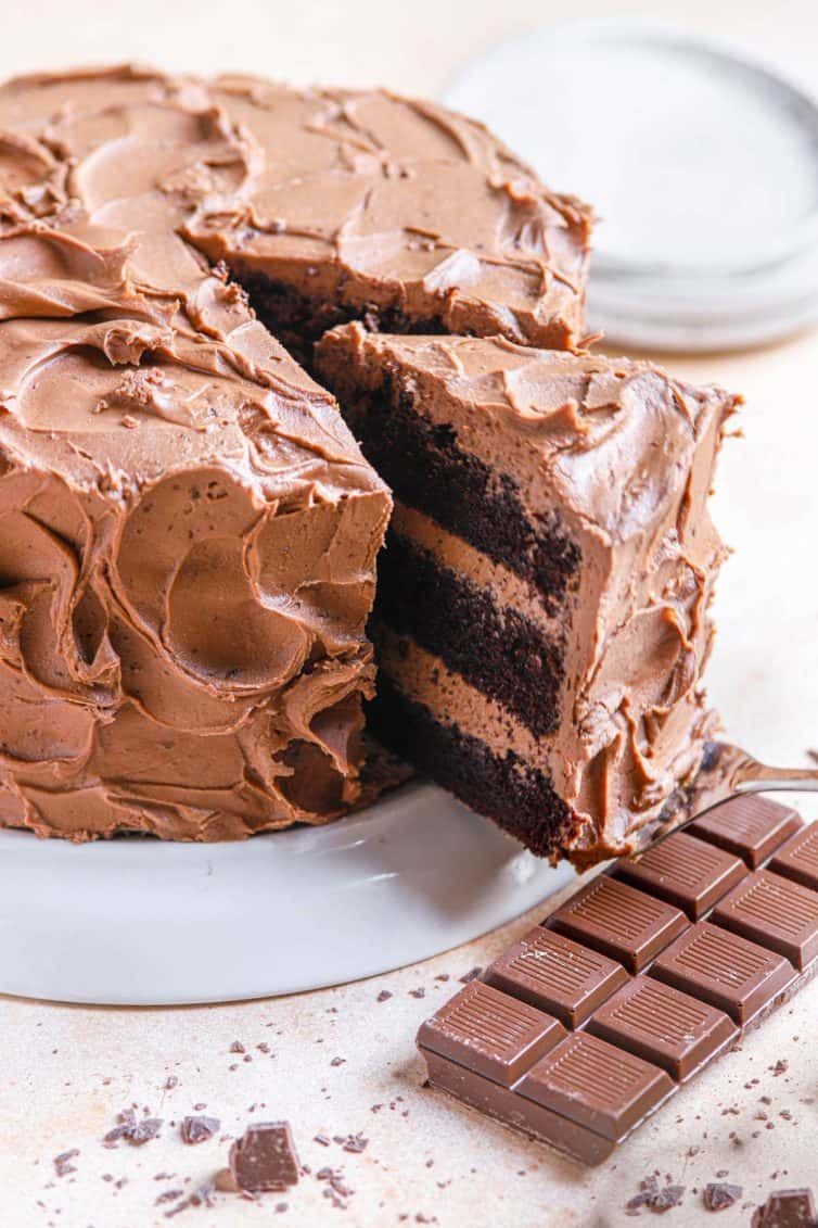 A chocolate cake on a cake stand with a slice of chocolate cake being removed and a chocolate bar in the bottom right.