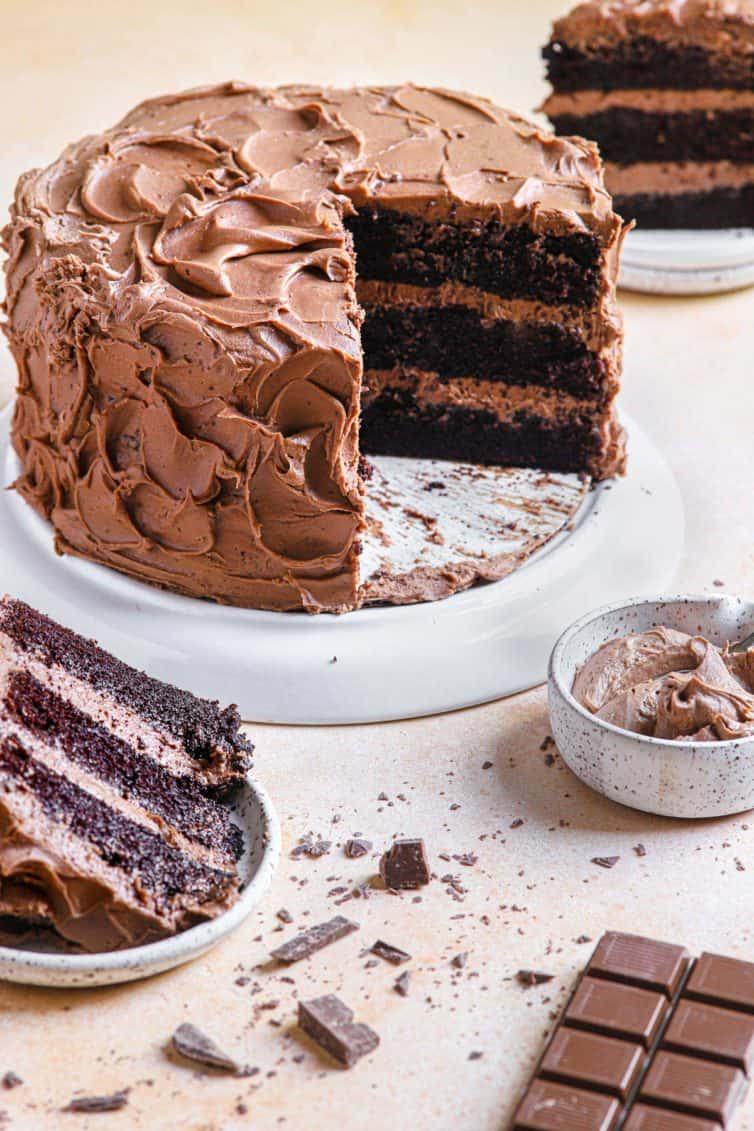 A chocolate cake on a white cake stand with chocolate cake slices in the back and front of the chocolate cake.