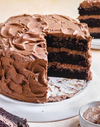 A chocolate cake on a white cake stand with slices removed to see the layers of the cake.