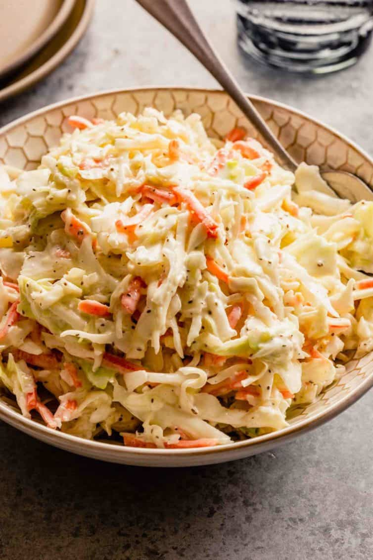 A bowl of creamy coleslaw with a silver spoon on a grey counter.