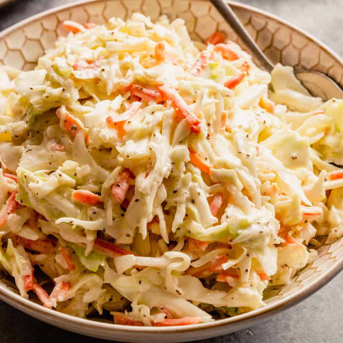 A white bowl with creamy homemade coleslaw and a silver spoon on the right side of the bowl.