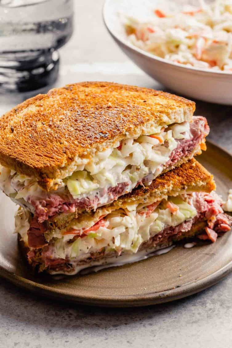 A sandwich with coleslaw inside on a brown plate.