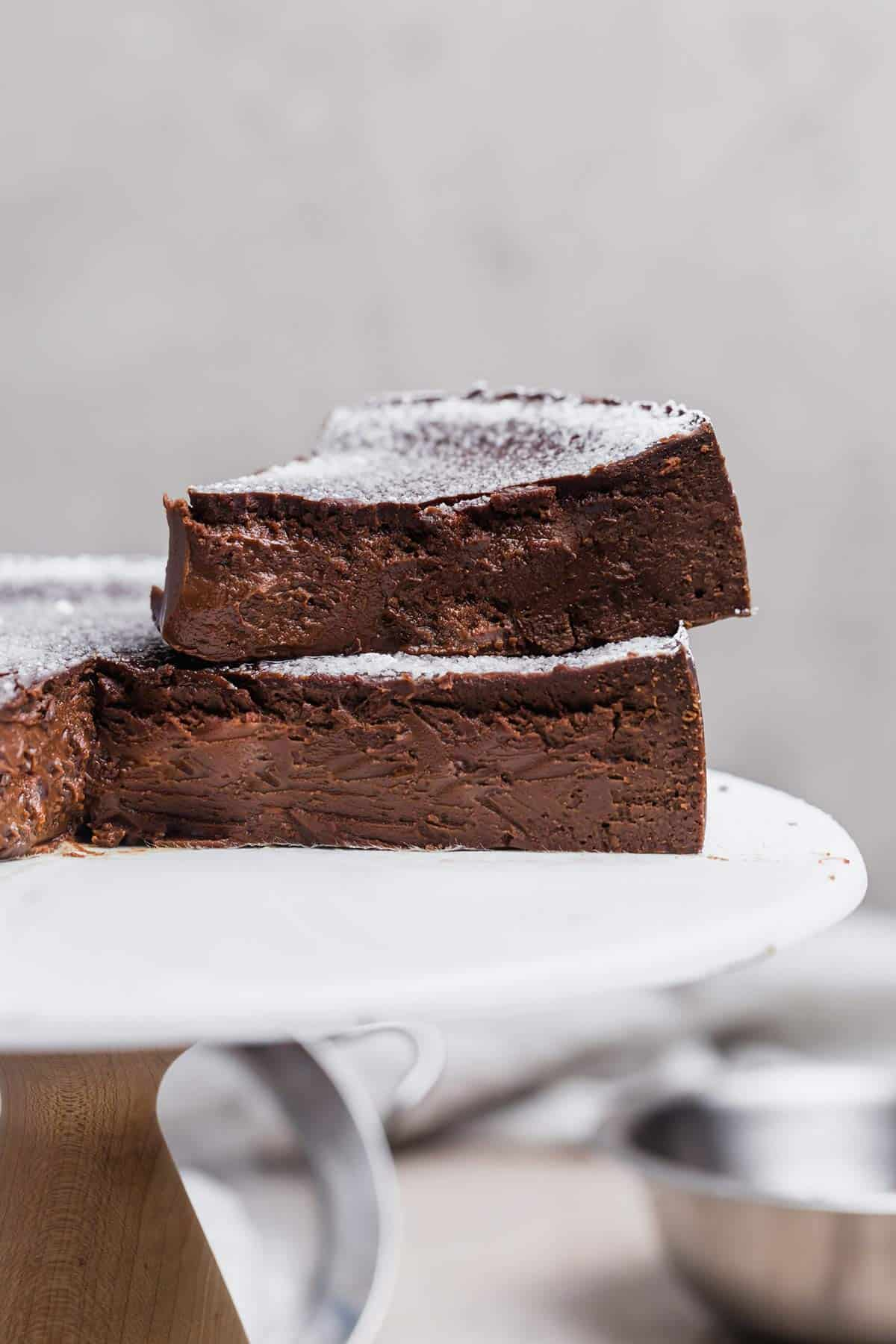 A slice of flourless chocolate cake on top of the chocolate cake on a white cake stand.