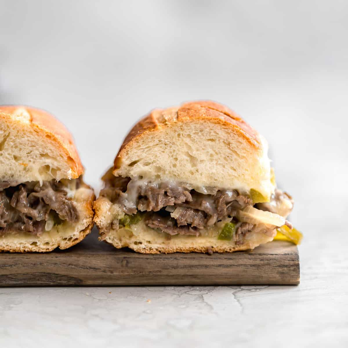 Two philly cheesesteak sandwiches on a wooden cutting board with the insides exposed showing the cheesy meat filling.
