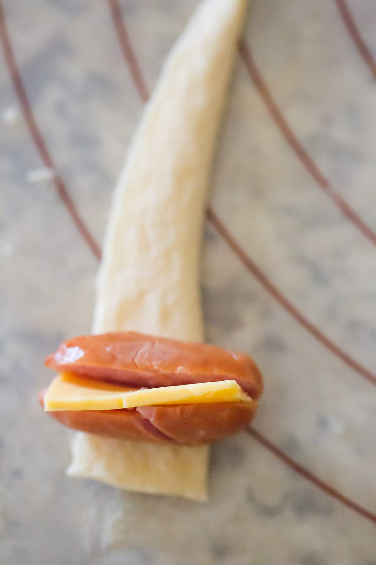 Mini hot dog with cheese stuffed inside sitting on strip of crescent roll dough.