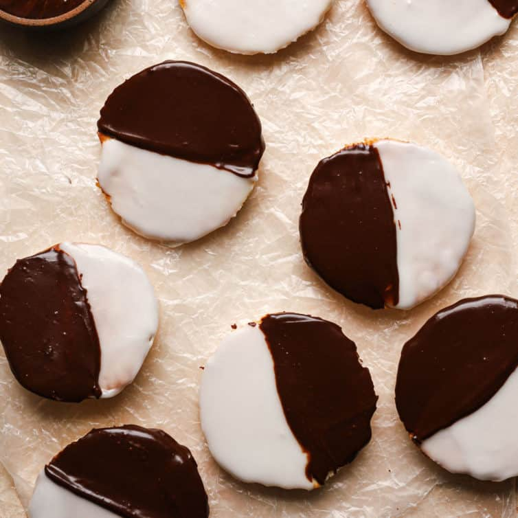 A square photo of black and white cookies on a counter covered in parchment paper.