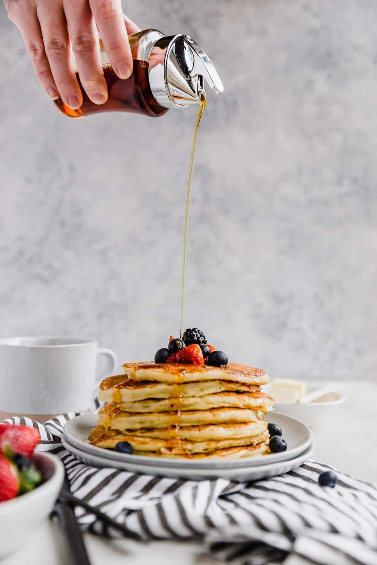 A hand pouring maple syrup over the stack of buttermilk pancaked topped with fresh berries on a blue and white striped towel.