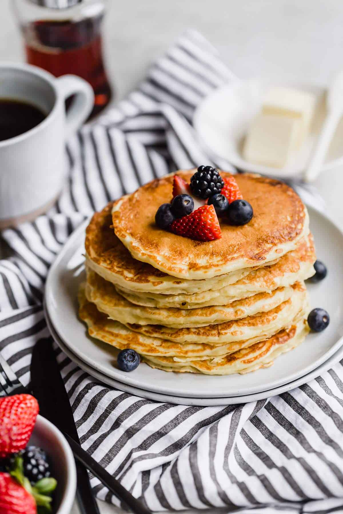 A stack of fluffy buttermilk pancakes topped with fresh berries on a white plate on a white and blue towel with syrup and butter in the back and a small bowl of strawberries in the bottom left corner.