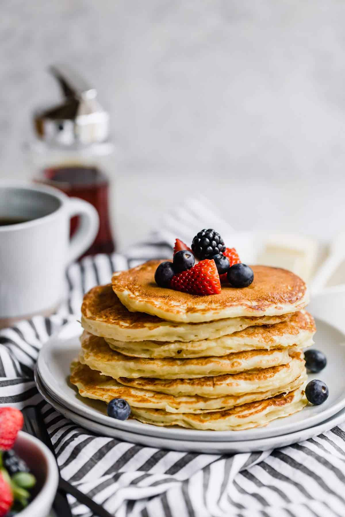 A stack of buttermilk pancakes on a blue and white striped towel with fresh berries on top and a jar of syrup in the back.