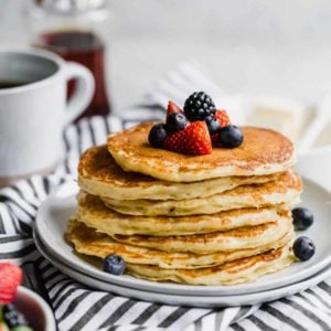 A stack of buttermilk pancakes topped with fresh berries on a white plate with a blue and white striped towel below.