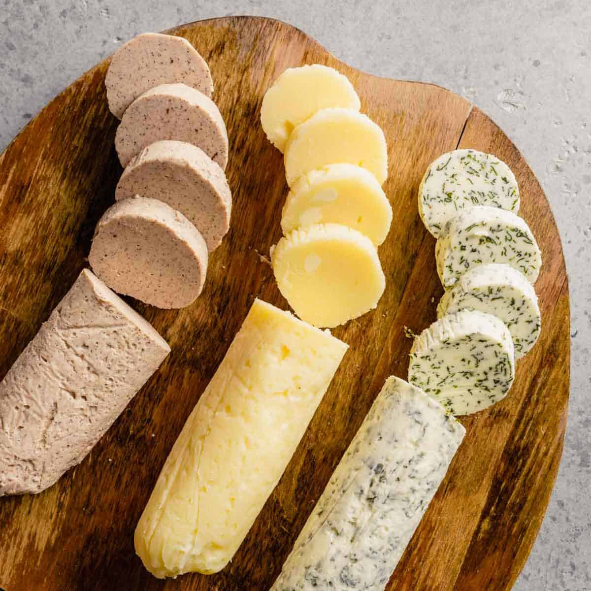 Three different compound butters cut in slices on a wooden cutting board.