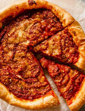 A close up of a deep-dish pizza with two slices cut out on a piece of parchment paper.