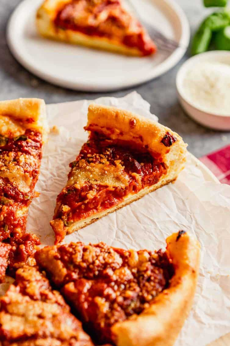 A deep dish pizza on parchment paper with a slice pulled out in the back.
