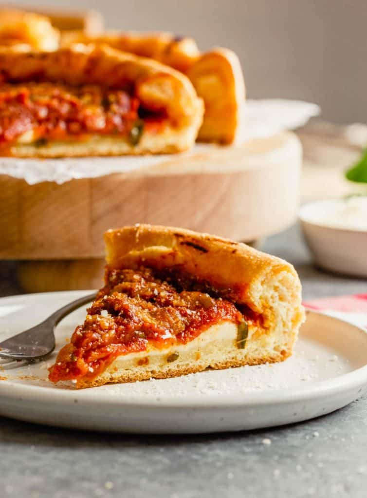 A slice of Chicago-style deep dish pizza on a white plate with a pizza in the back.