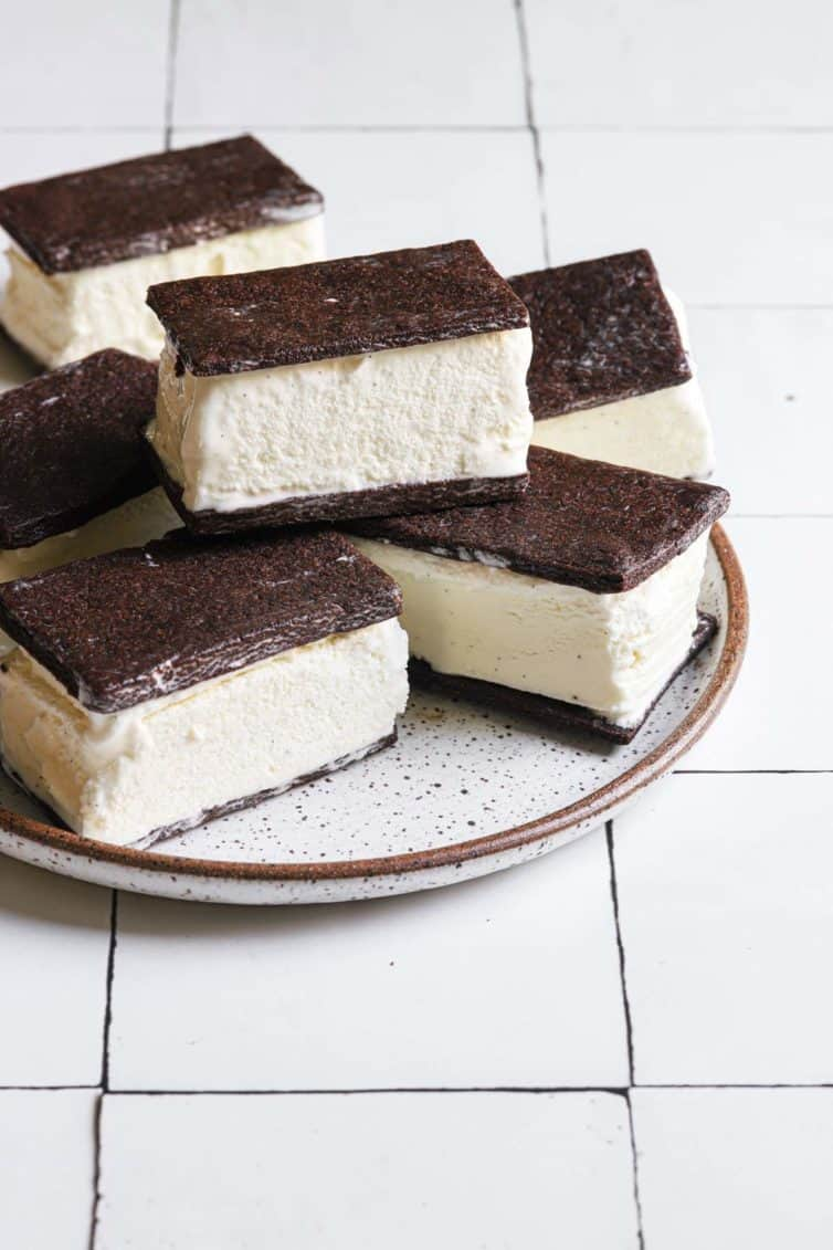 Homemade ice cream sandwiches on a white plate with a brown rim.