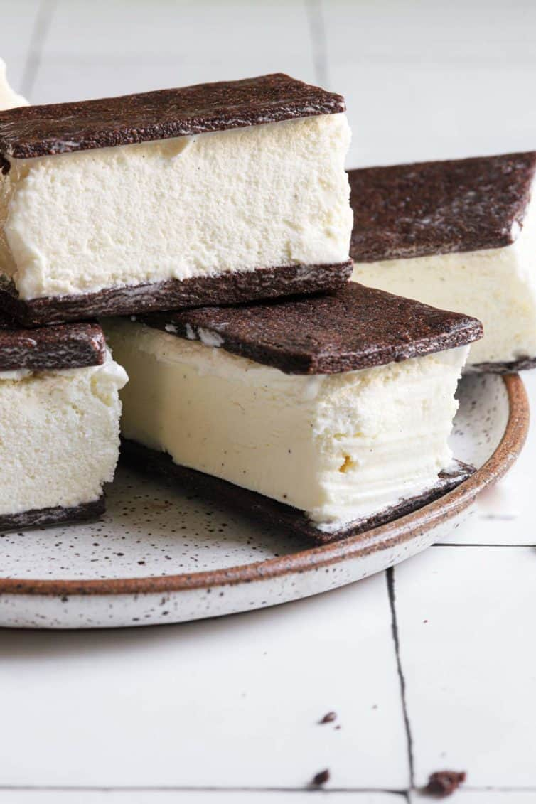 A plate with ice cream sandwiches on a white plate with a brown rim.