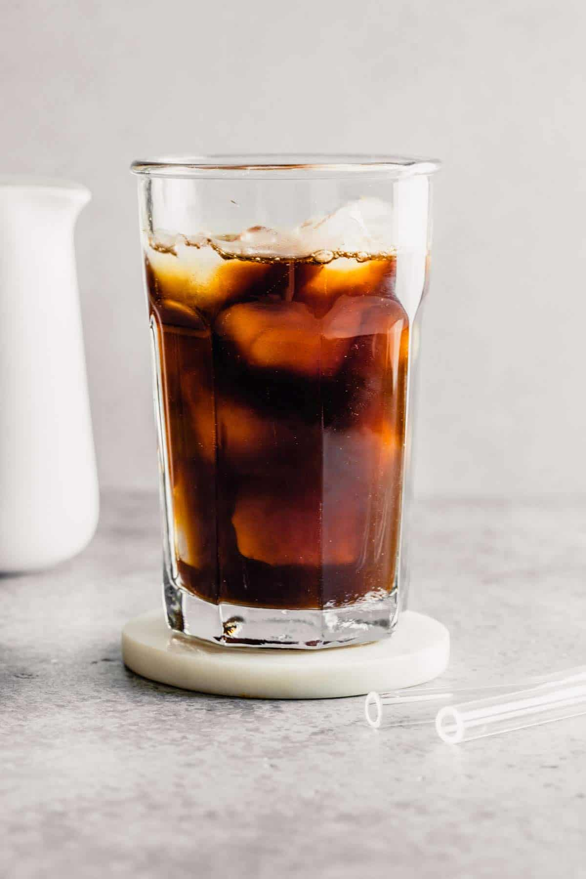 A glass of iced coffee on a coaster with milk in the back left.