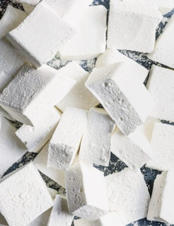 Marshmallows in a pile with the ones on top turned to show the fluffy inside.