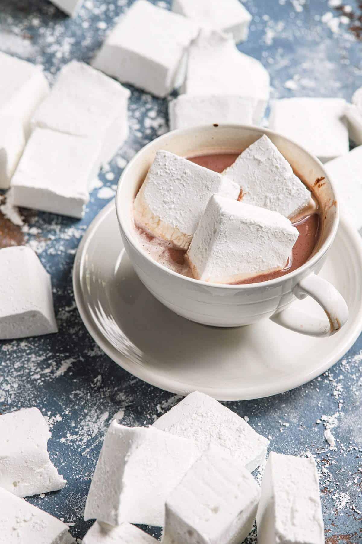 A white up of hot chocolate topped with marshmallows and marshmallows on the blue counter around it.
