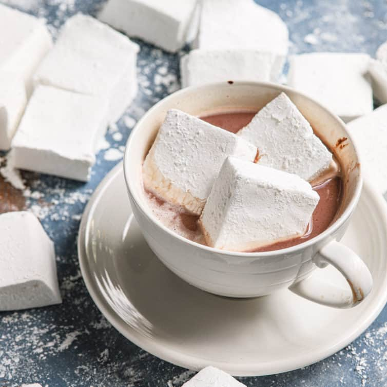 A close up of the white mug and saucer of hot chocolate with three marshmallows on top.