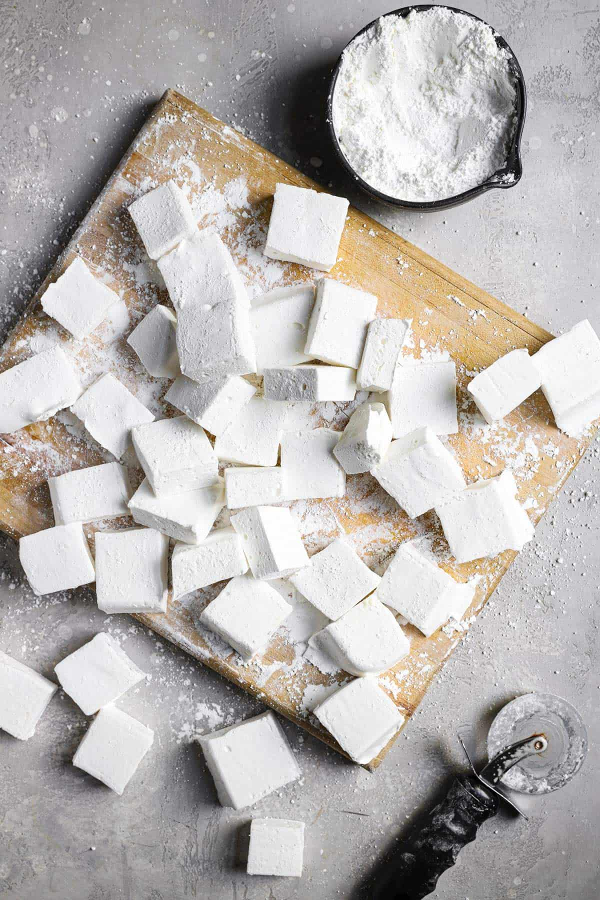 A top down photo with a wooden cutting board in the middle with fresh marshmallows and a rolling cutter in the bottom right corner.
