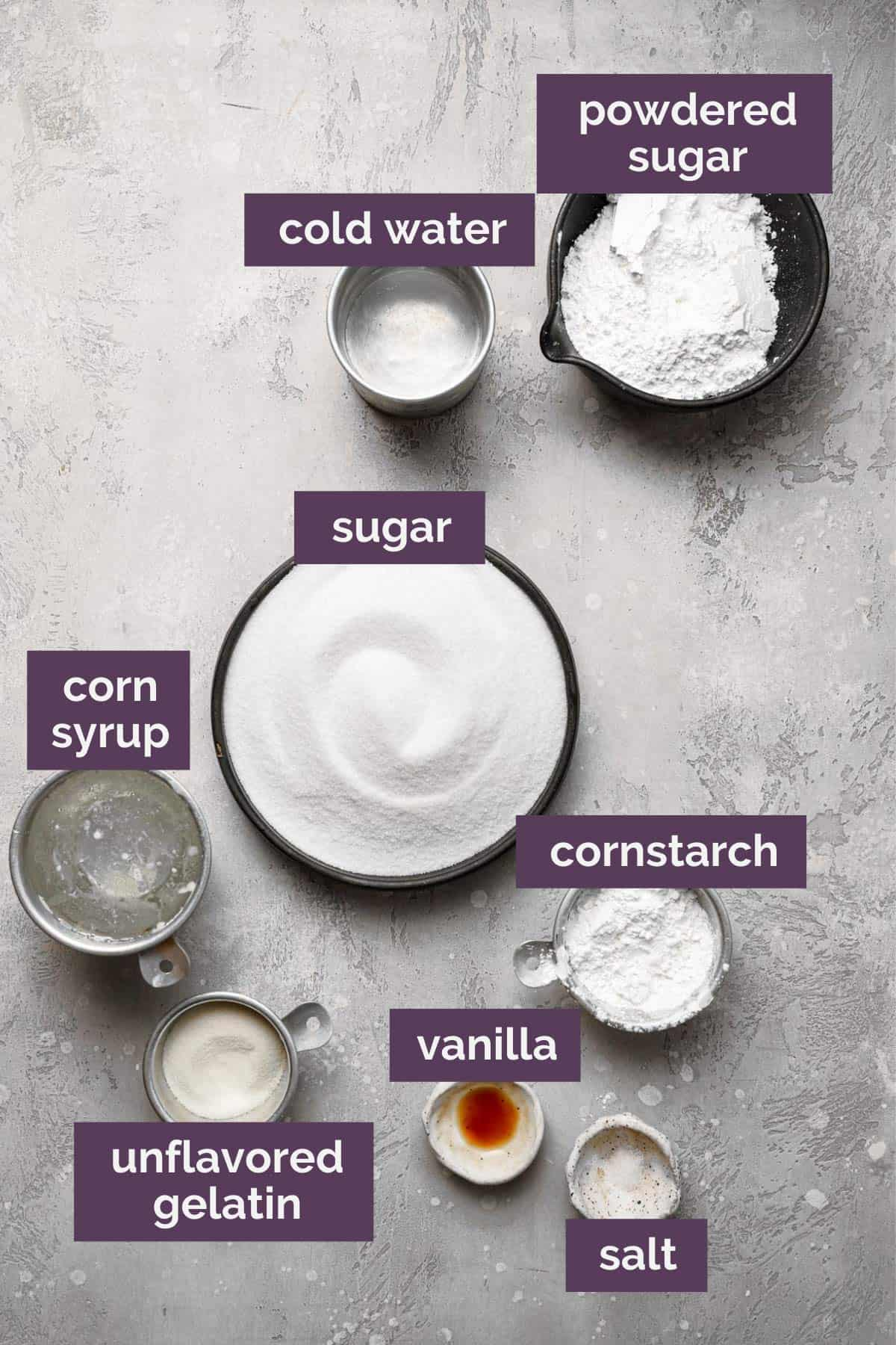 Ingredients for marshmallows on a grey counter with purple labels over the ingredients.