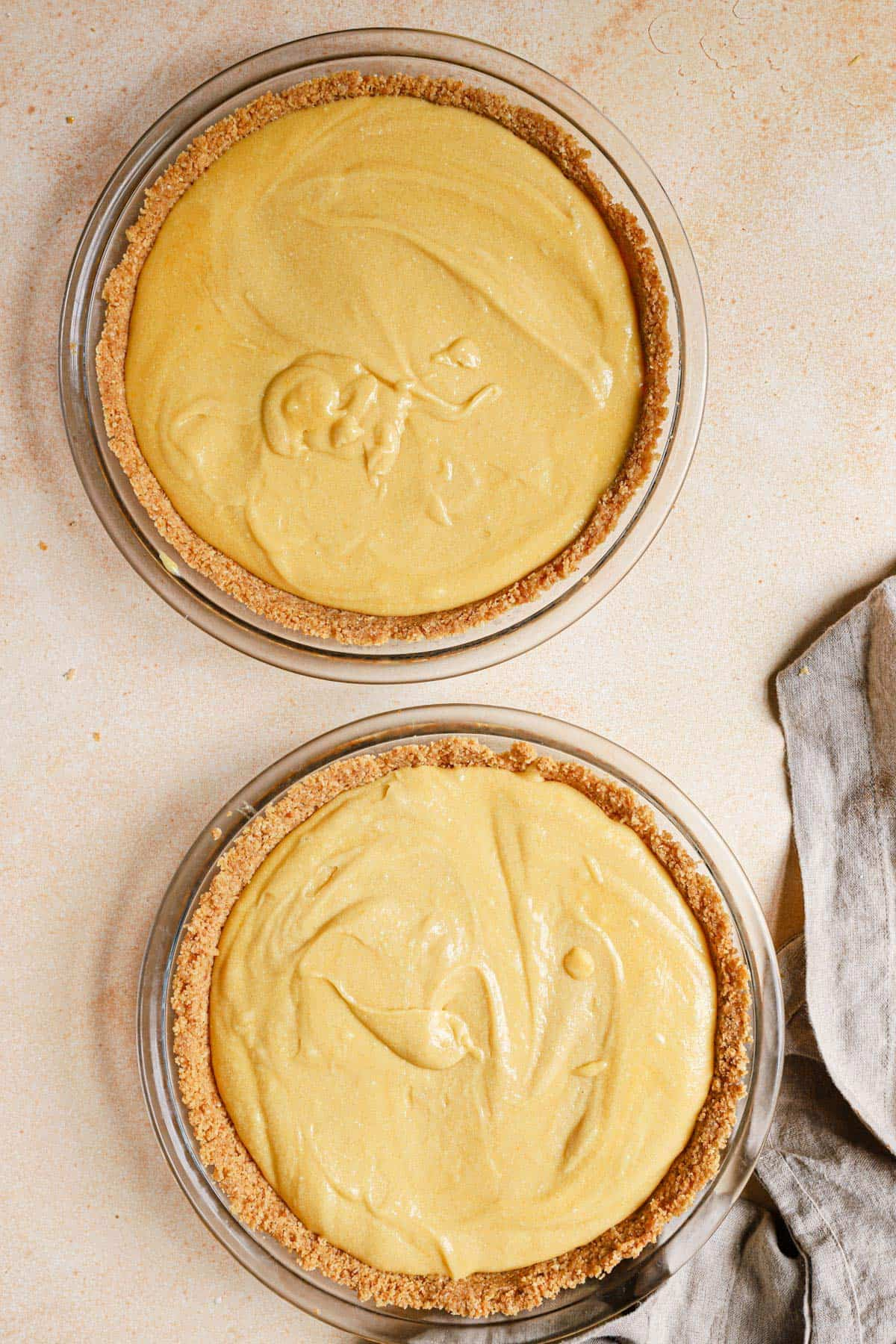 Two milk bar pies before baking on a peach colored counter with a dish towel to the bottom right.