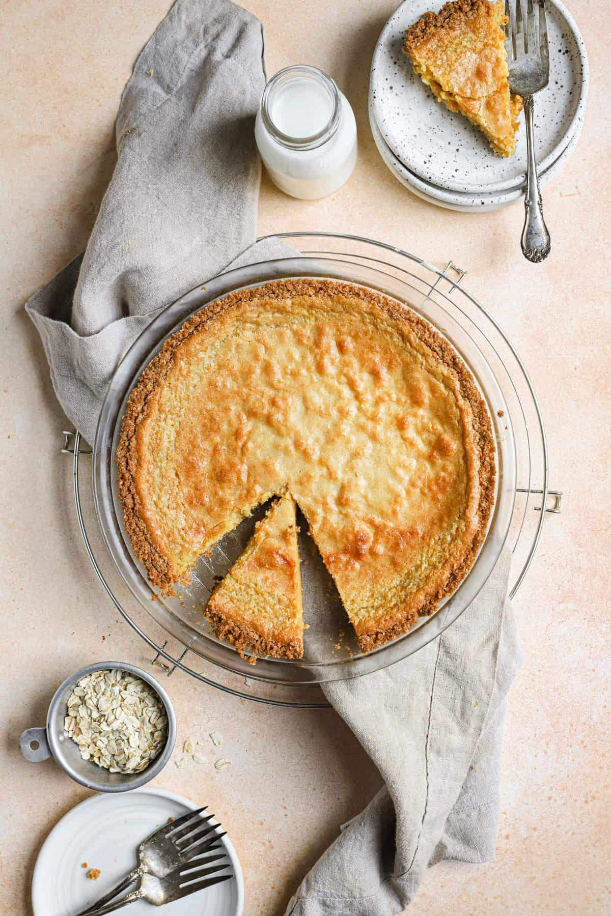 Crack pie on a round cooling rack with a slice on a plate in the top right and a slice cut out in the pie plate with a towel under the pie pan.