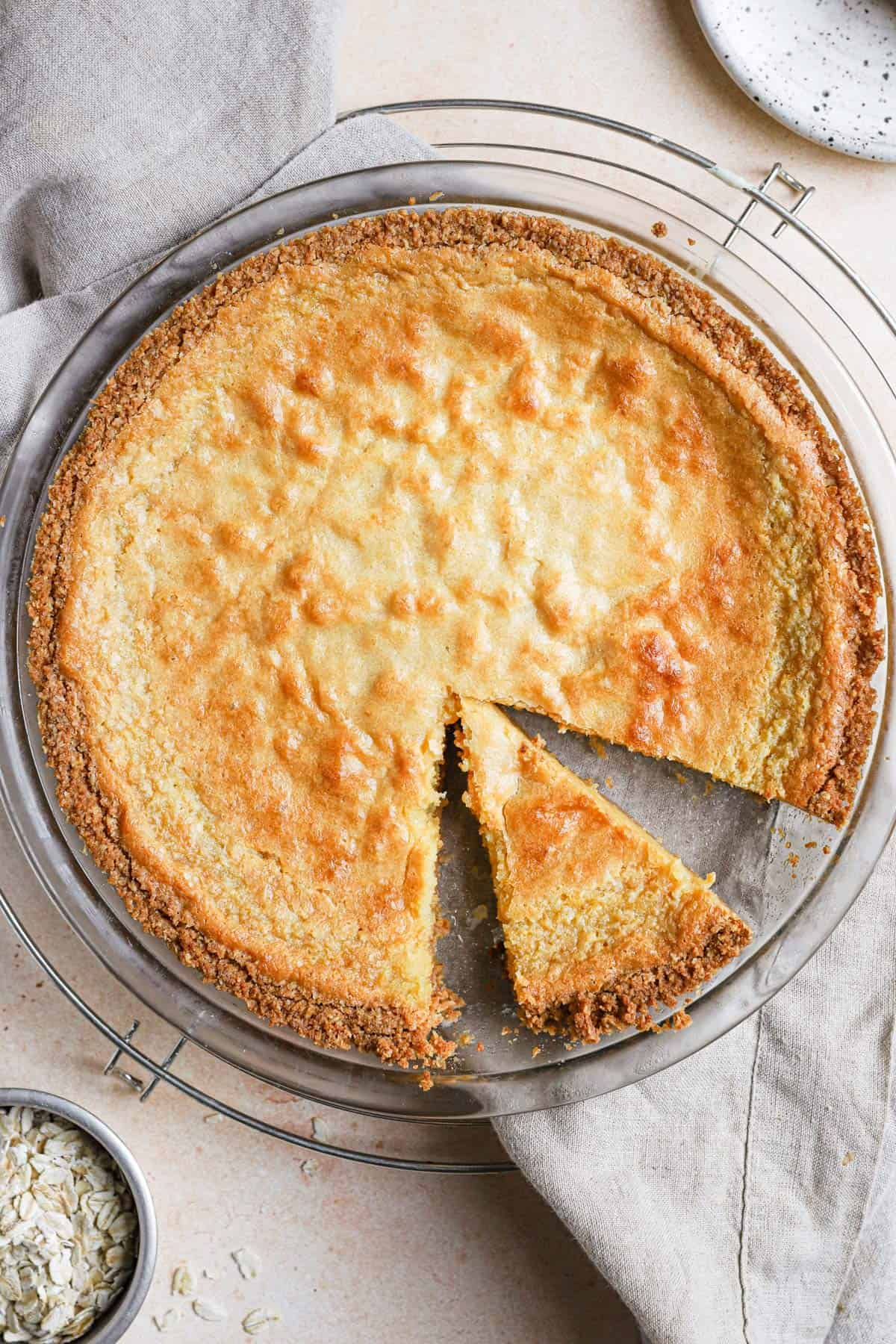 A momofuku crack pie in a pie pan on a cooling rack with a slice cut in the right bottom side of the pie.